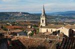 Im Hintergrund der Kirche von Bonnieux befindet sich das kleine Örtchen Lacoste.